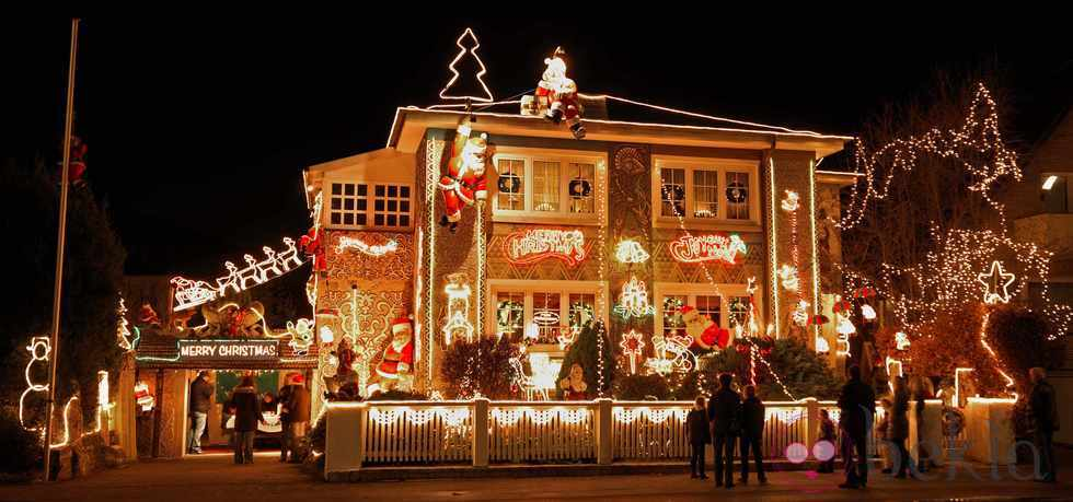 People walking in front of a seasonal decorated house in the Niendorf district of Hamburg, northern Germany, admire the colorful Christmas illumination on Saturday evening, Nov. 28, 2009.