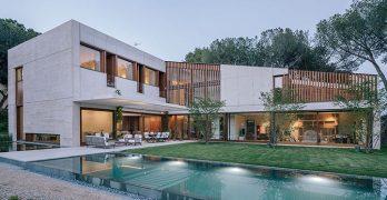 Casas moderna en forma de L ubicada en Madrid, fachada acristalada con piscina incluida